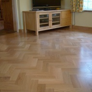 American Oak block in a herringbone pattern finished with Bona Traffic lacquer. Skirting board to match.